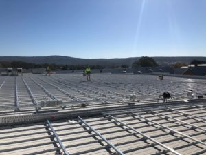 workers installing solar panels on the roof of a grocery store