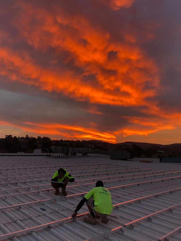 workers installing solar panels on the roof of a grocery store during sunset