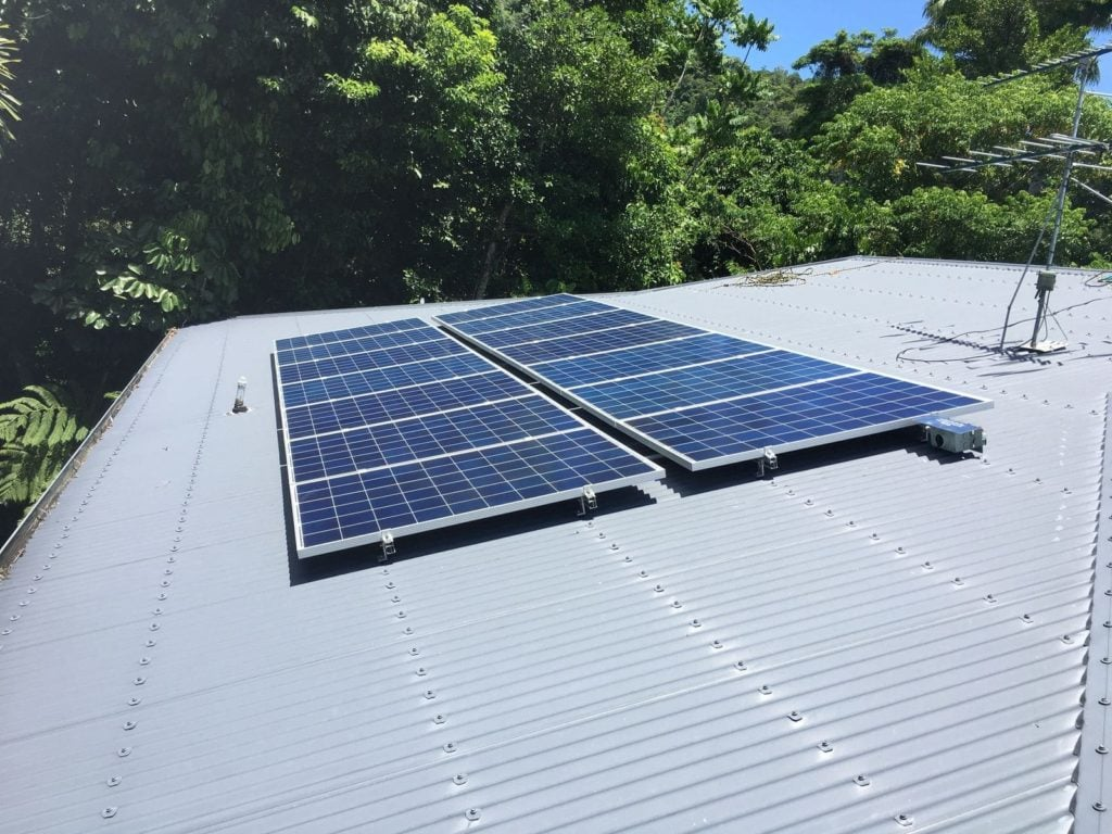 solar panels on a roof with trees in the background