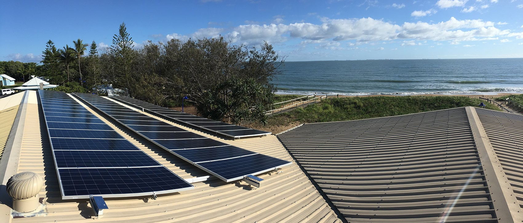 solar panels on a roof with the sea in the background