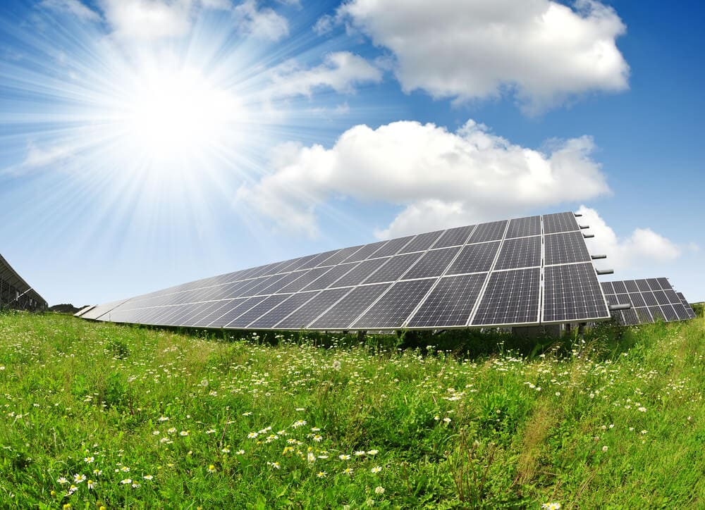 solar panels on a green field with the sun and blue skies in the background