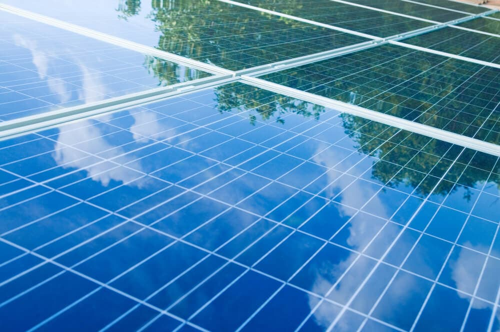 solar panels with reflections of tree and clouds