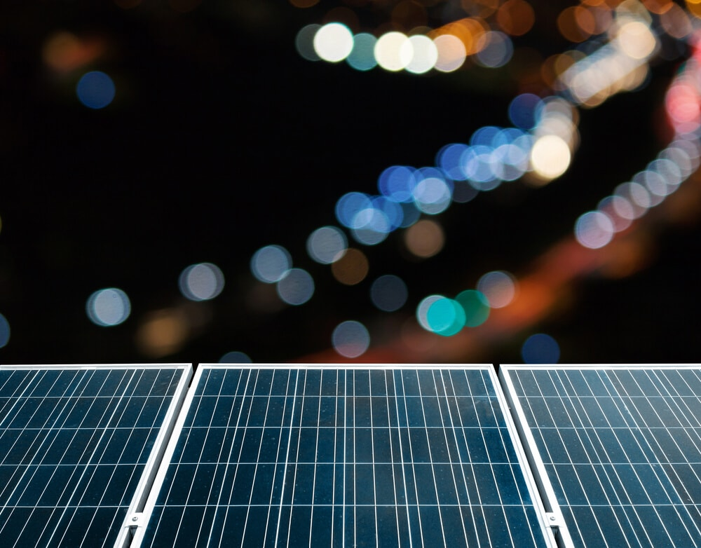 solar panels at night with city lights in the background